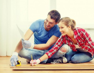 smiling-couple-measuring-wood-flooring